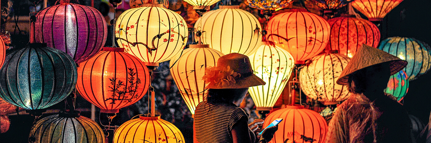 two people in front of orange and yellow paper lamps