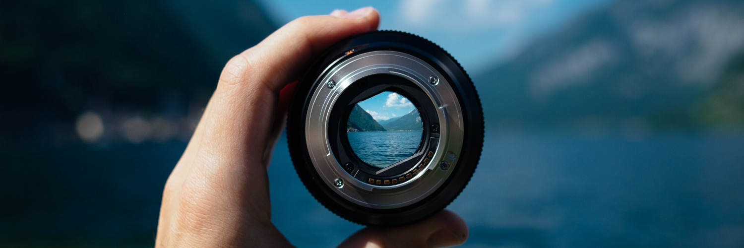 camera lense in focus, background is a mountain scenery