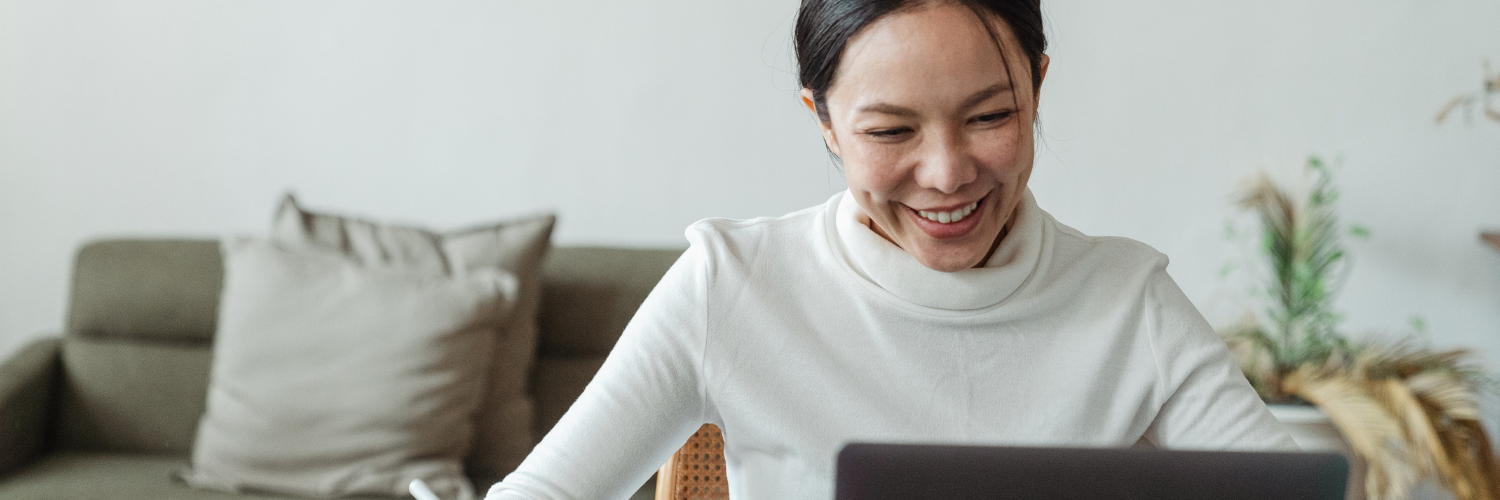 asian woman smiling in front of laptop while communicating with colleagues
